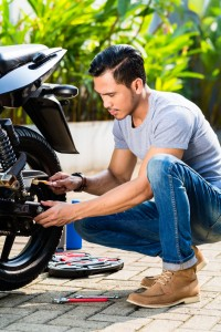 37846977 - asian man doing motorcycle maintenance in his garden